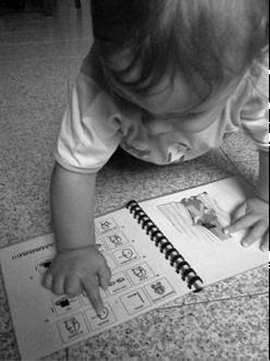 un bambino molto piccolo indica un simbolo in un libro